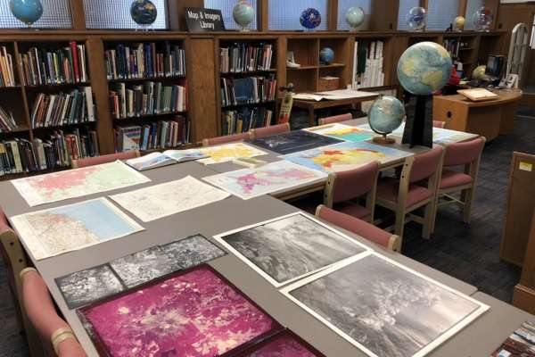 Photographs and maps laid out on a table surrounded by book cases and globes in the Map and Imagery Library
